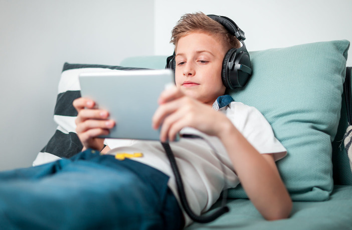 Teenage boy using tablet with headphones lying on bed in his room 50